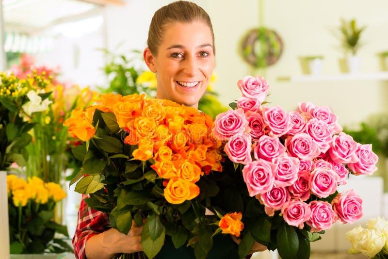 Kvinnligblomsterhandlare i blomsterhandel arkivfoto