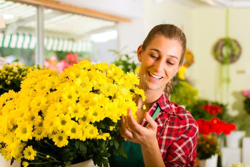 Kvinnligblomsterhandlare i blomsterhandel arkivbild