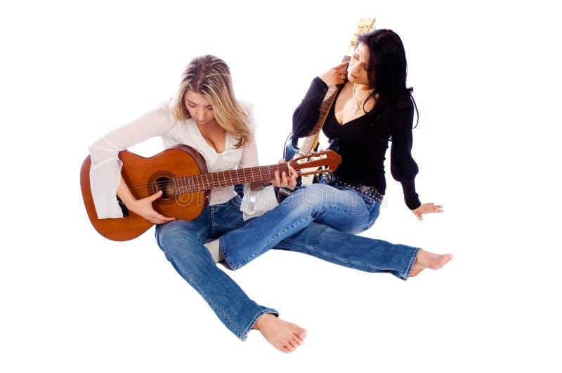Kvinnliggitarrister som trimmar deras gitarrer royaltyfri bild