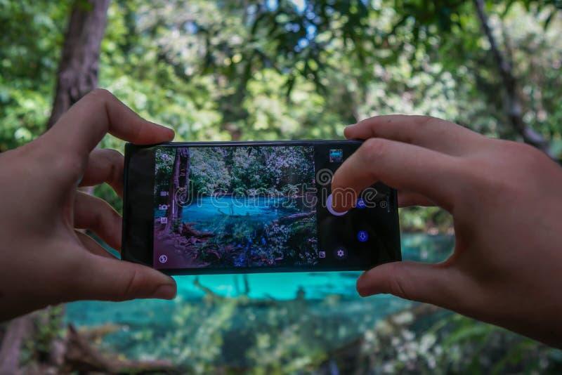 Kvinnlighänder genom att använda mobiltelefonen för att ta fotoet av Sra Morakot Blue Pool på det Krabi landskapet i Thailand Ber arkivfoto