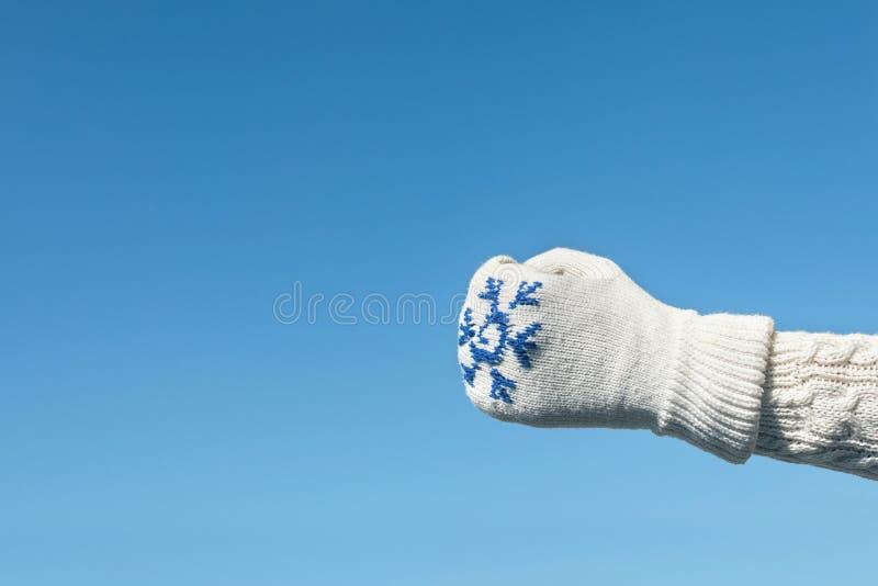 Kvinnlighänder i vintern stack tumvanten på den klara bakgrunden för blå himmel arkivfoto