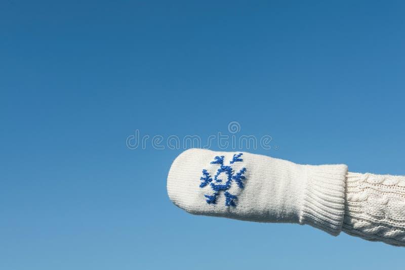 Kvinnlighänder i vintern stack tumvanten på den klara bakgrunden för blå himmel arkivbild