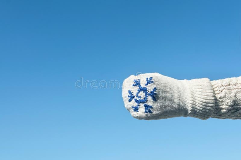 Kvinnlighänder i vintern stack tumvanten på den klara bakgrunden för blå himmel royaltyfria bilder