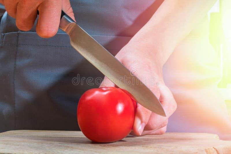 Kvinnlighänder med kniven som klipper den mogna röda tomaten på träbräde Varm solig lapp av ljus royaltyfria bilder