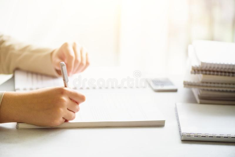Kvinnlighänder med pennhandstil på anteckningsboken tillbaka begreppsskola till Student från universitet som lär språk royaltyfria bilder