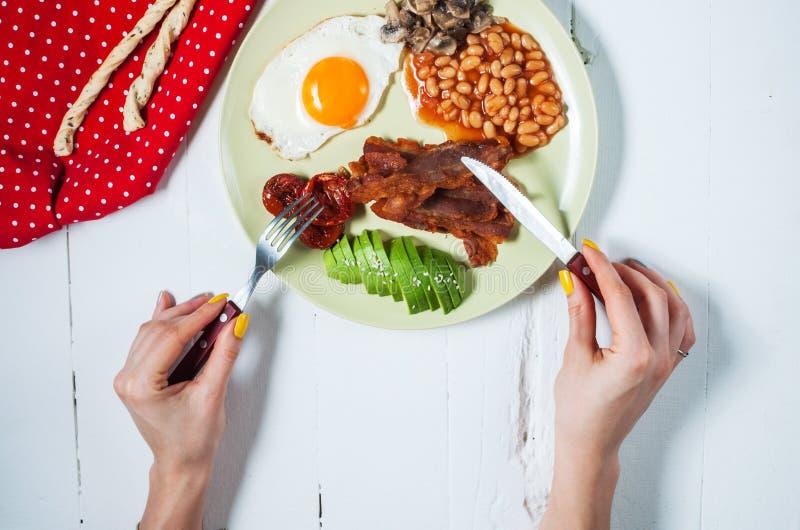 Kvinnlighänder och engelsk frukost på den vita wood tabellen royaltyfri bild