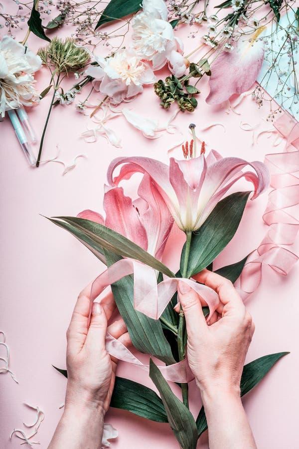 Kvinnlighänder som gör den älskvärda rosa liljan, blommar buketten på den pastellfärgade tabellen med blomsterhandlaregarneringut arkivfoto