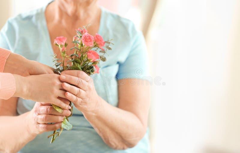 Kvinnlighänder som ger blommor till kvinnan royaltyfri foto