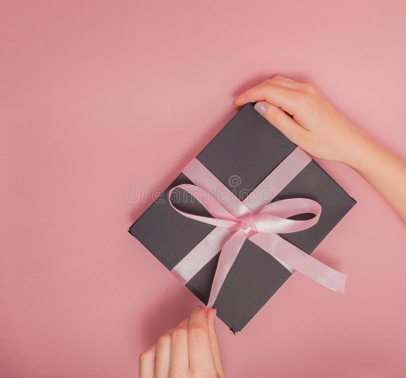Kvinnlighänder som packar upp gåvaasken Kvinnlign manicured gående knöt upp gåvaasken för händer med rosa färger bugar Ferie och  arkivfoto