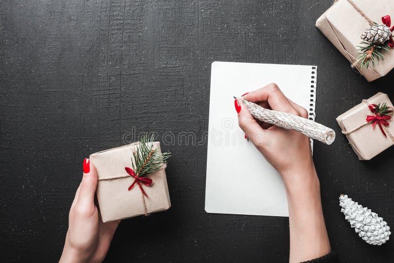 Kvinnlighänder som skrivar julbrevet med gåvor och garneringar lägger framlänges, den bästa sikten Begrepp för Xmas och för nytt  arkivbild