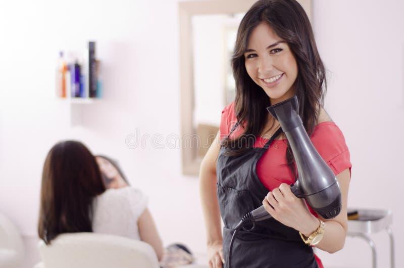 Kvinnlighairstylist som fungerar i en salong arkivbild