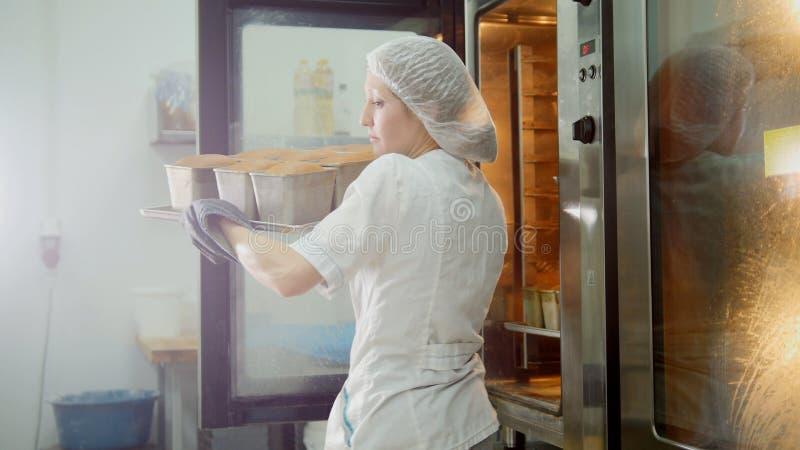 Kvinnlign bakar på kommersiellt kök - handtag brödet från ugnen fotografering för bildbyråer