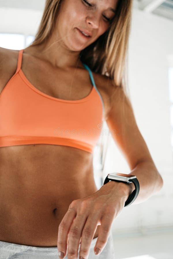 Kvinnlign efter genomkörareperiod kontrollerar resultat på smartwatch i kondition app Den färdiga kvinnan ser den smarta klockan  arkivbilder