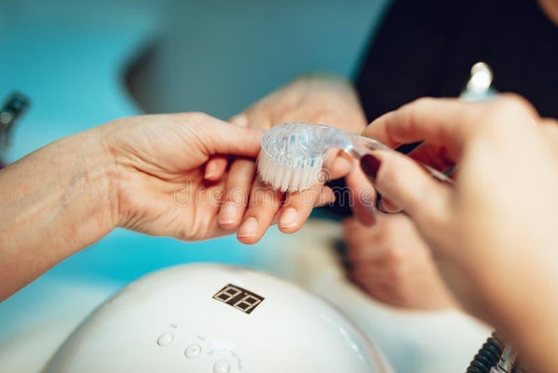 kvinnlign hands manicurebehandling royaltyfri fotografi