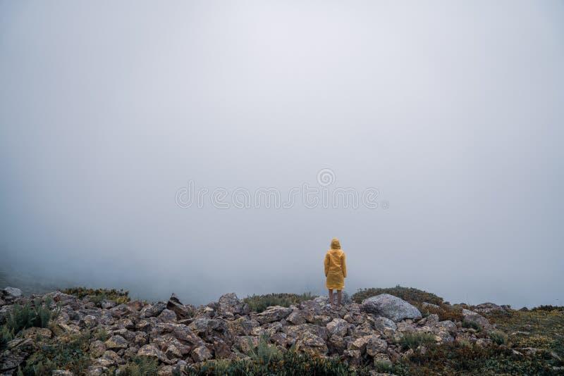 Kvinnlign i den gula regnrocken, jeans kortsluter anseende överst av berget med sikt av maxima på horisonten Landskap Natur royaltyfri foto
