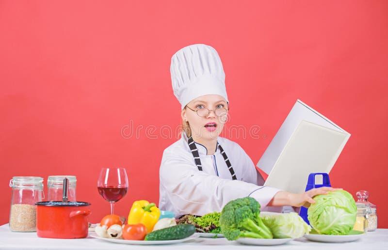 Kvinnlign i hatt och f?rkl?de vet allt om kulinariska konster Kulinarisk expert Kvinnakock som lagar mat sund mat flicka arkivfoto
