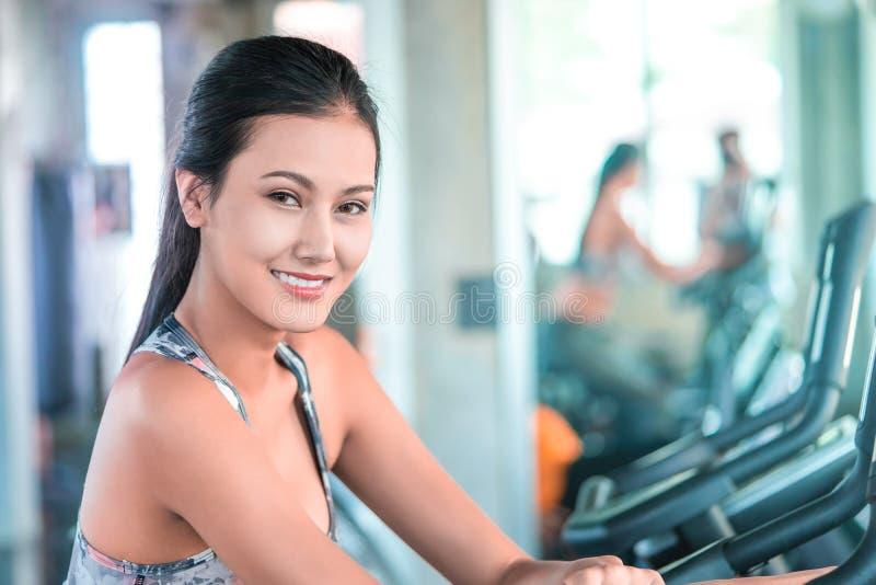 Kvinnlign i militära sportwearsportkläder utarbetar på momentklättraremaskinen i konditionidrottshallen för sunt livsstilbegrepp fotografering för bildbyråer