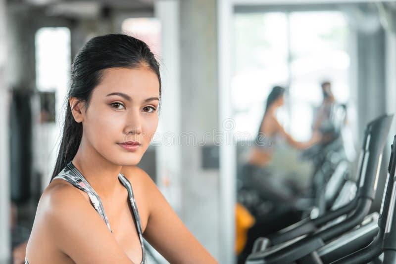 Kvinnlign i militära sportwearsportkläder utarbetar på momentklättraremaskinen i konditionidrottshallen för sunt livsstilbegrepp arkivbilder