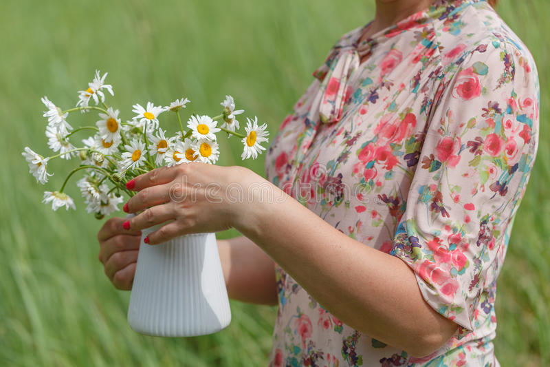 Kvinnlign i sommar parkerar hållbuketten av tusenskönablommor royaltyfria foton