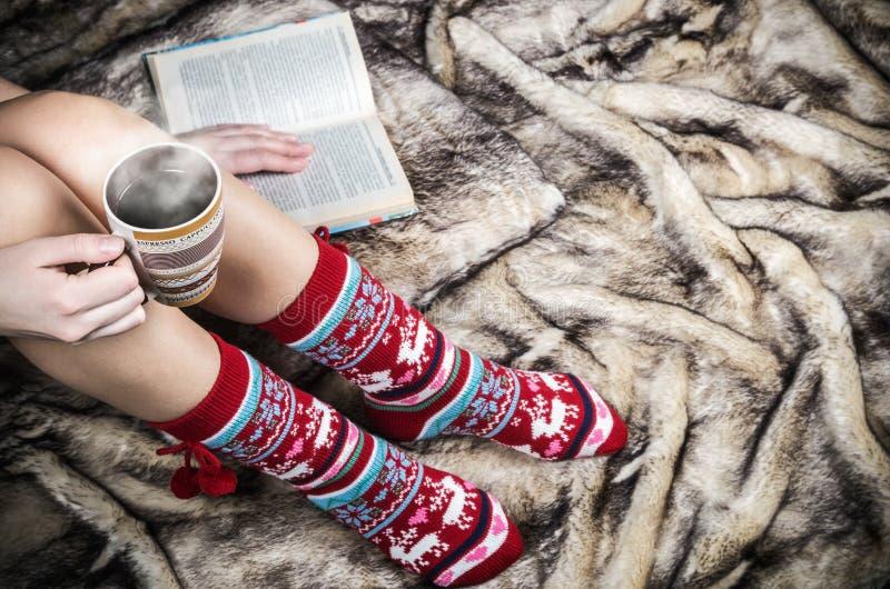 Kvinnlign lägger benen på ryggen i julsockor med en bok och en kopp kaffe royaltyfria foton