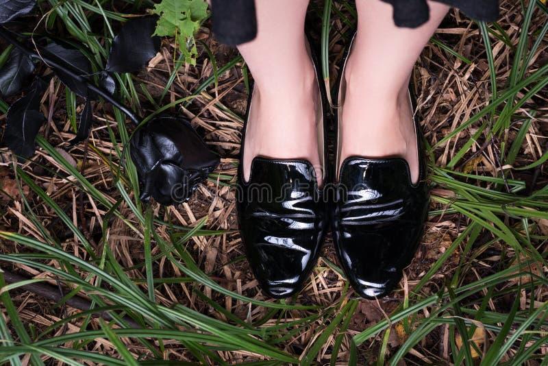 Kvinnlign lägger benen på ryggen i svarta skor för patenterat läder på gräset royaltyfria bilder