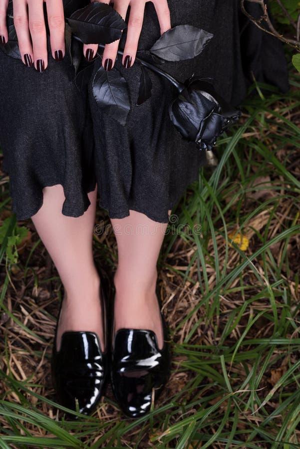 Kvinnlign lägger benen på ryggen i svarta skor för patenterat läder på gräset Svart kjol och en ros fotografering för bildbyråer