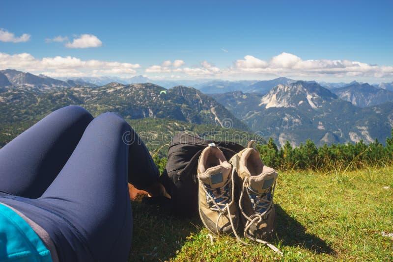 Kvinnlign lägger benen på ryggen, kängor och ryggsäcken mot alpina berg fotografering för bildbyråer