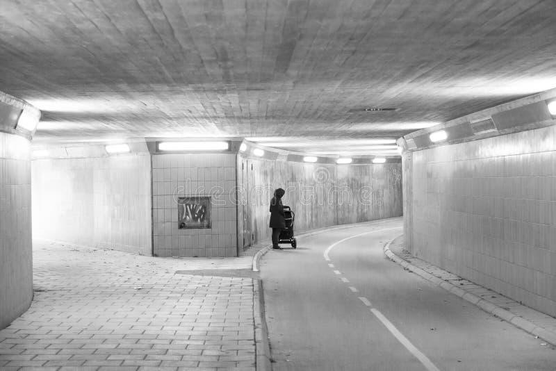 Kvinnlign med behandla som ett barn sittvagnen i tunnel arkivfoton