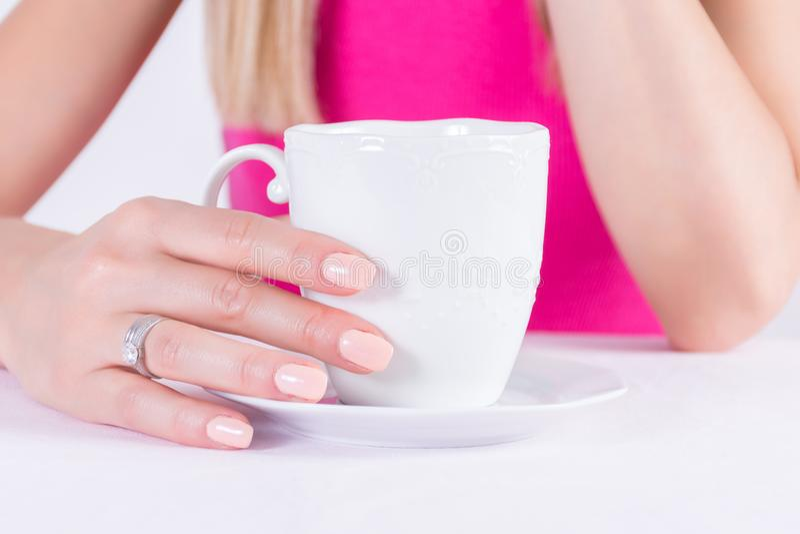 Kvinnlign med näck färgmanikyr spikar polermedel stelnar och diamantcirklar på den hållande kaffekoppen för fingret arkivfoto