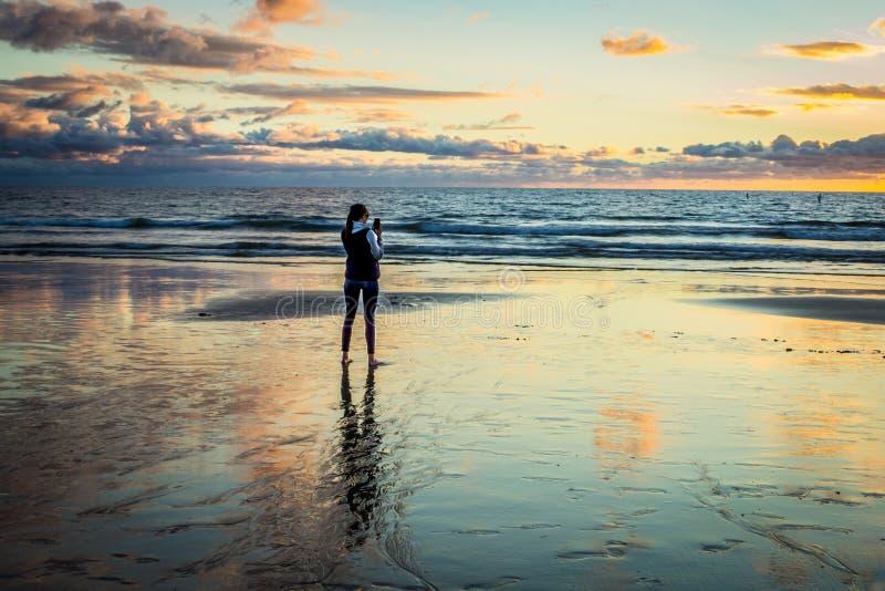 Kvinnlign på stranden tar bilden av solnedgången med cellen arkivfoton