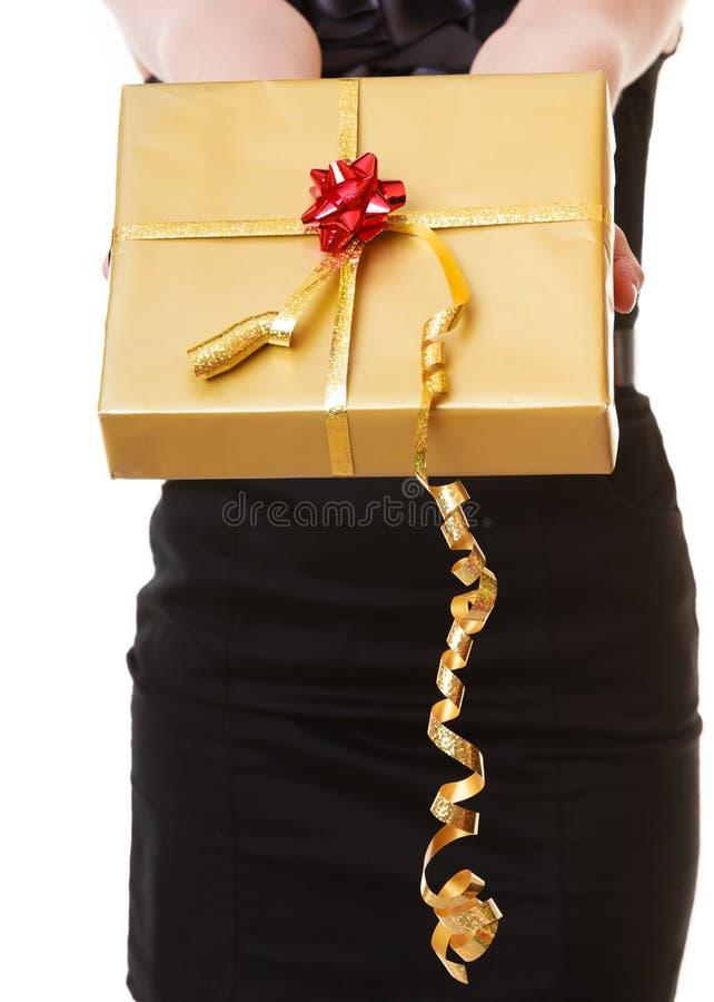 Kvinnlign räcker att ge jul den guld- gåvaasken med bandet. Ferie. arkivbild