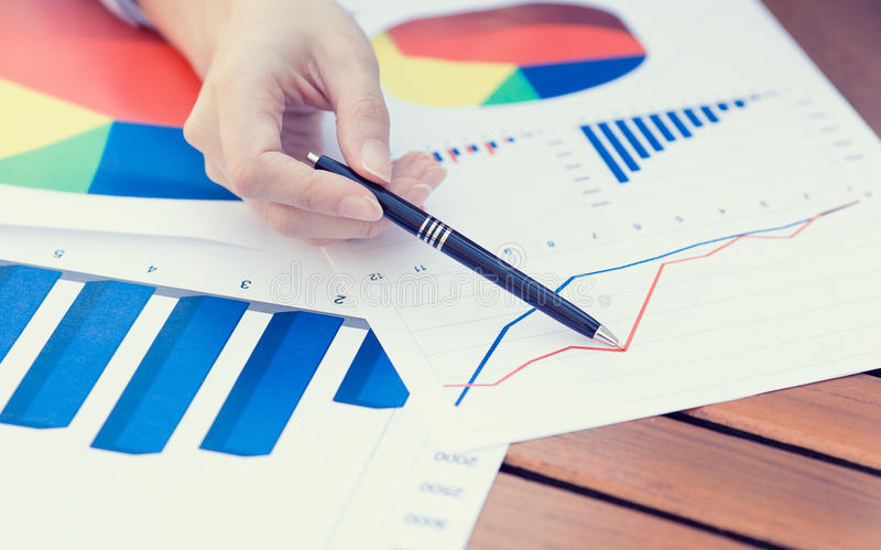 Kvinnlign räcker att peka med pennan på det finansiella rapportdiagrammet för affären arkivfoton