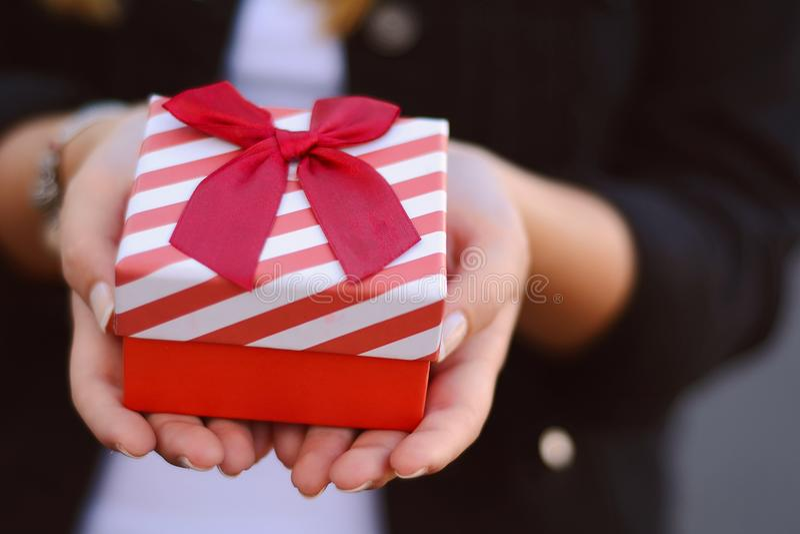 Kvinnlign räcker att rymma en gåvaask, gåva arkivfoto