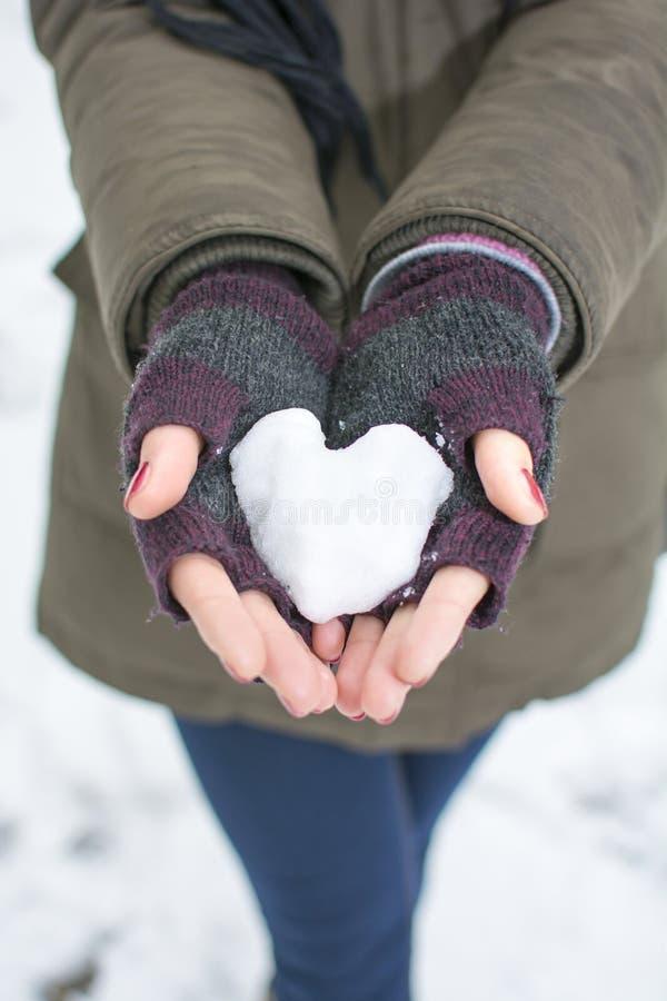 Kvinnlign räcker att rymma en hjärta gjord ut ur snö arkivfoton