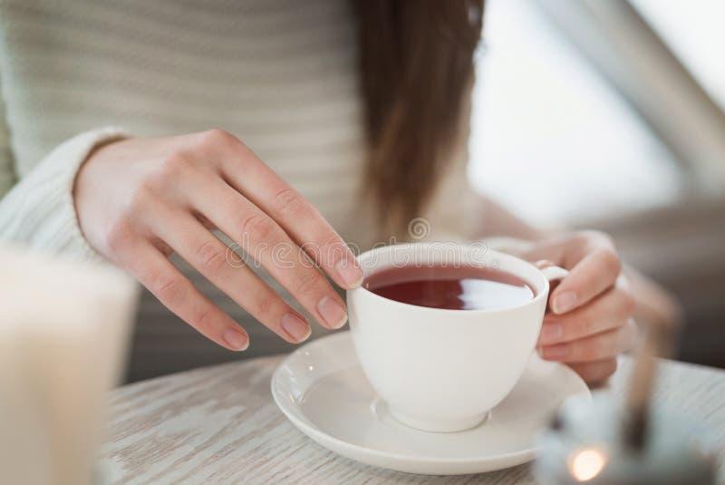 Kvinnlign räcker att rymma ett vitt kopp teanseende på den bästa sikten för tabellen royaltyfri bild