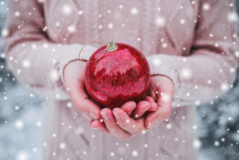 Kvinnlign räcker att rymma jul den röda bollen Frostig vinterdag i snöig skog royaltyfri foto