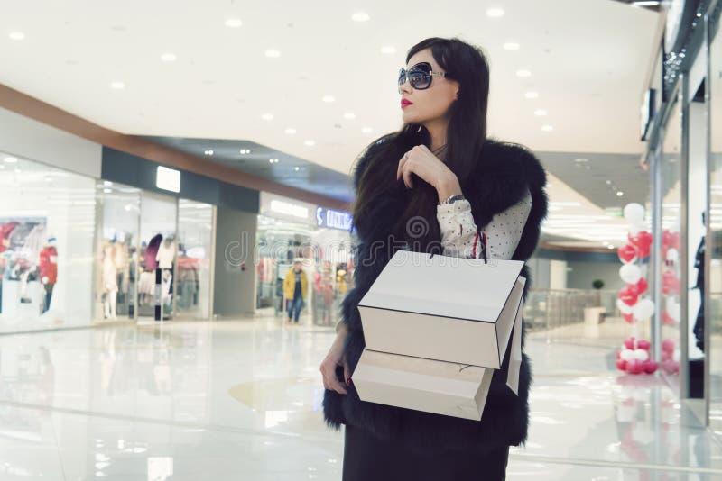 Kvinnlign räcker att rymma påsar för en shopping arkivfoto