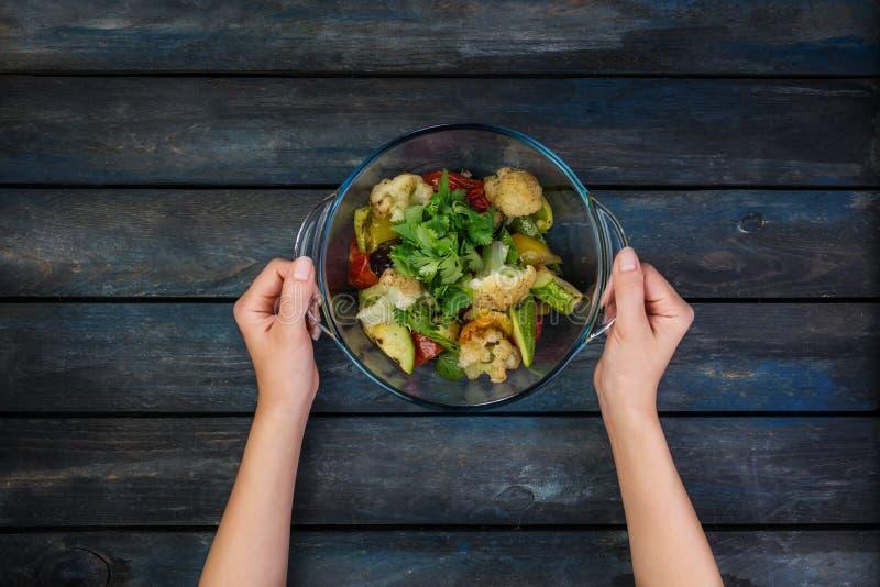 Kvinnlign räcker att rymma plattan med grillad grönsaksallad med zucchinin, aubergine, lökar, peppar och tomaten överkant royaltyfria foton