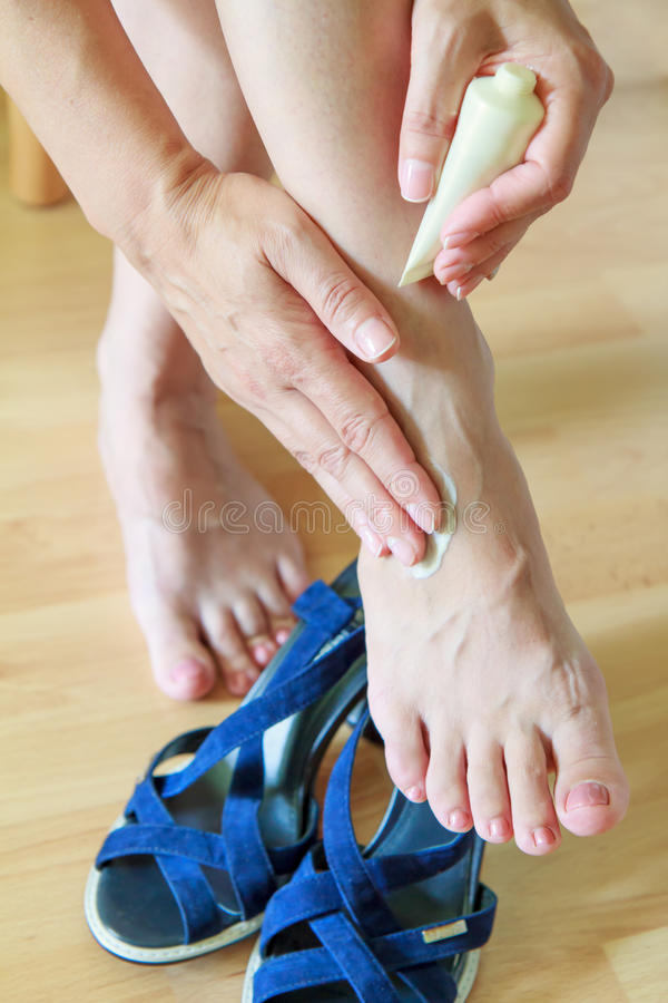 Kvinnlign räcker att trycka på och att laga mat med grädde ett naket göra ont och svälla f arkivfoton