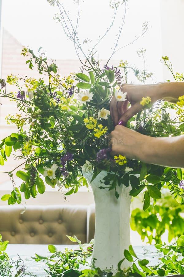 Kvinnlign räcker danandevasen med sommarbuketten som göras från lösa blommor för fältet på en tabell i modern vardagsrum på fönst royaltyfria foton