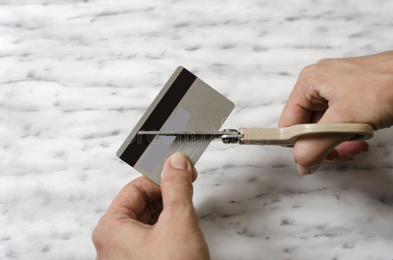 Kvinnlign räcker den bitande kreditkorten med sax fotografering för bildbyråer