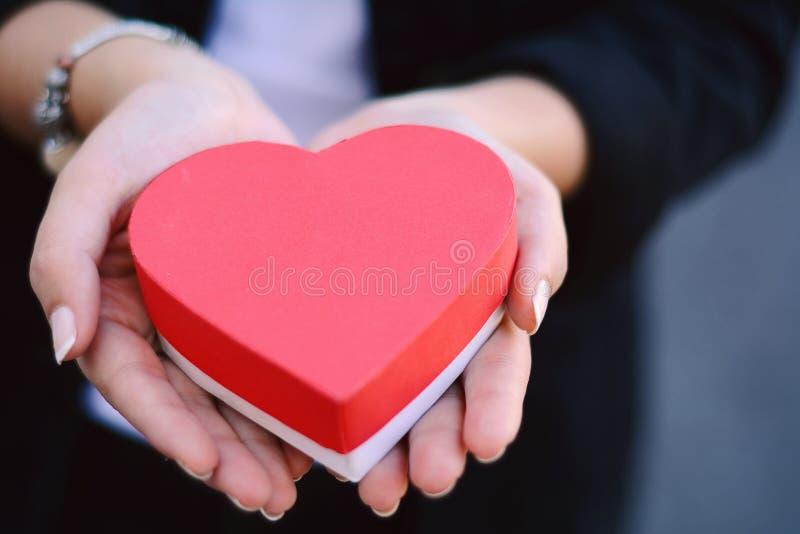 Kvinnlign räcker den hållande hjärta formade gåvaasken arkivbild