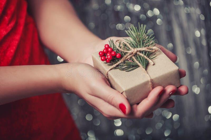 Kvinnlign räcker den hållande julgåvaasken med filialen av granträdet, skinande xmas-bakgrund Feriegåva och garnering royaltyfria foton