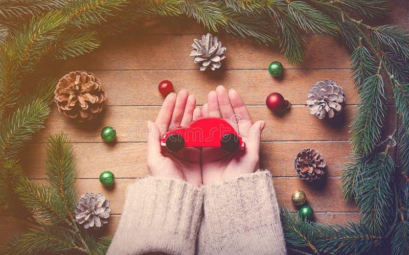 Kvinnlign räcker den hållande julleksakbilen på trätabellen arkivfoto