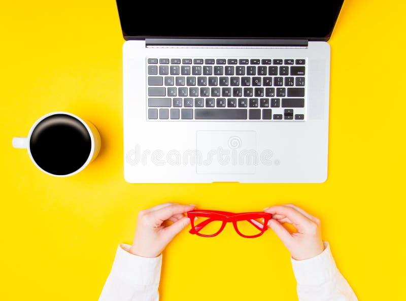 Kvinnlign räcker hållande glasögon nära koppen kaffe och bärbara datorn arkivbild