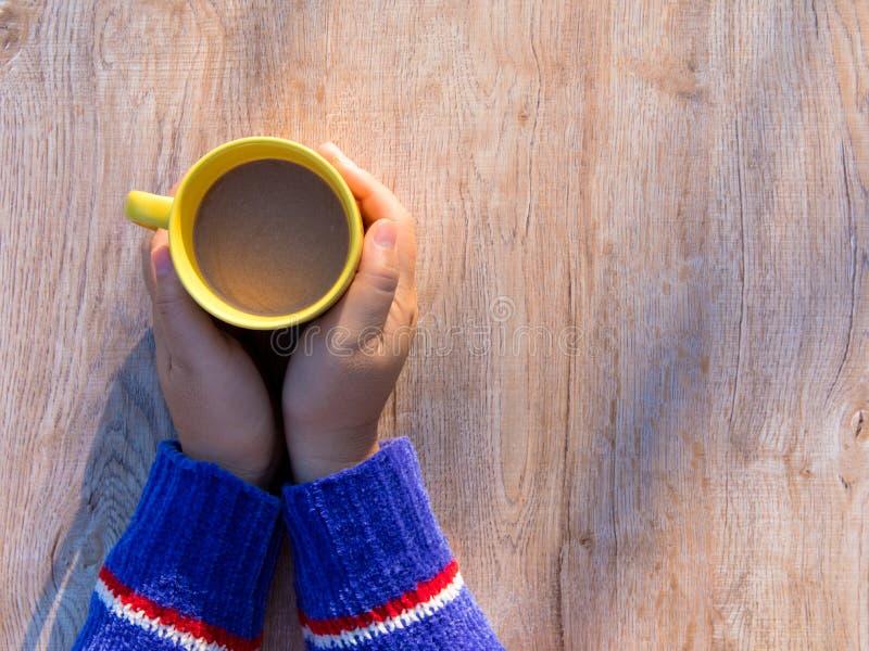 Kvinnlign räcker hållande koppar kaffe på lantlig trätabellbakgrund arkivbilder