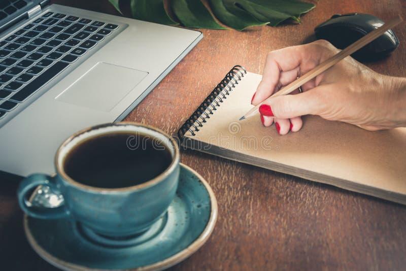Kvinnlign räcker handstil på anteckningsboken books begreppslivstid nära gammal yellow för writing för tappning för pennquillscro royaltyfri fotografi
