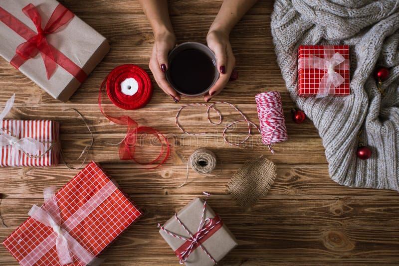 Kvinnlign räcker inpackning av julklappar i pappers- och band dem med röda och vittrådar och en kopp te arkivfoto