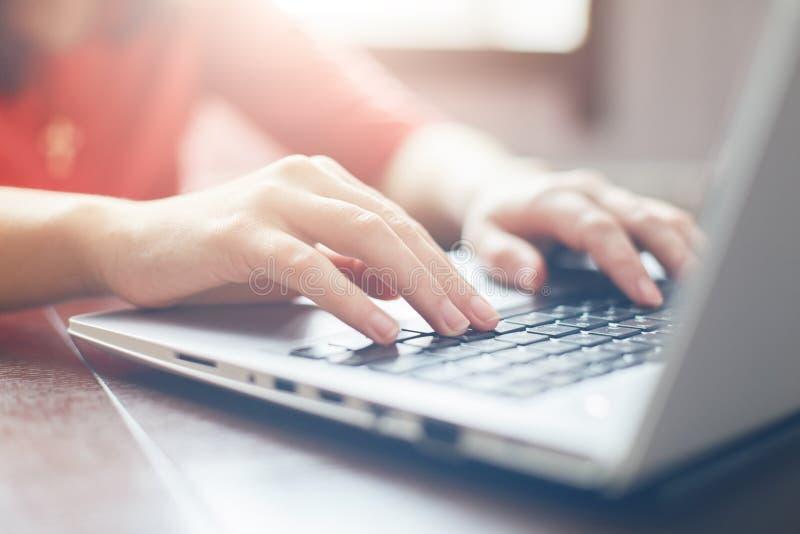 Kvinnlign räcker maskinskrivning på tangentbordet av bärbara datorn som surfar internet och smsar vänner via sociala nätverk som  arkivfoto