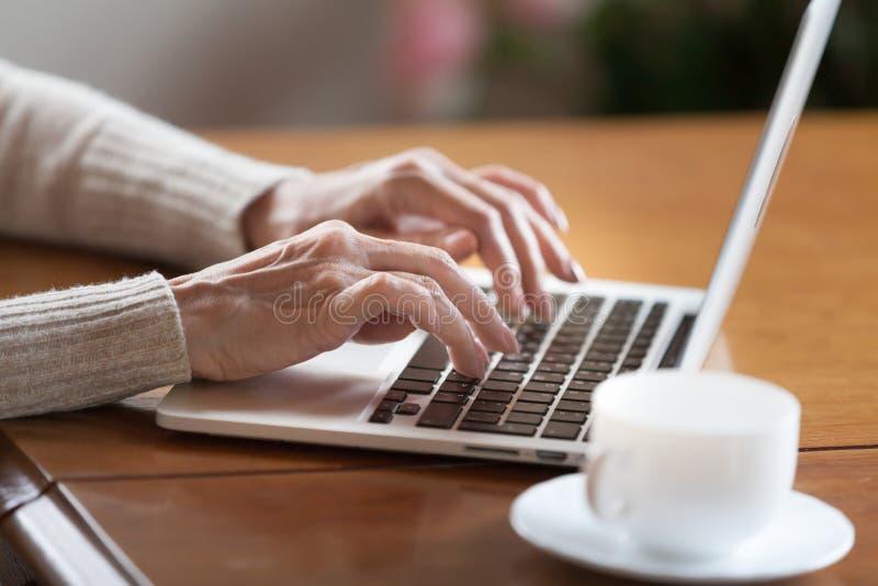 Kvinnlign räcker maskinskrivning på tangentbordet, den höga kvinnan som arbetar på bärbara datorn royaltyfri foto